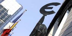 Fahnenmasten und eine Figur, welche das Eurozeichen in die Luft hält, vor blauem Himmel